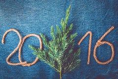 Ramo fresco da árvore de Natal e os números 2016 de corda em t Imagem de Stock