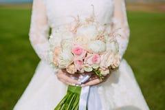 Ramo hermoso de la boda de flores en las manos de la novia Foto de archivo