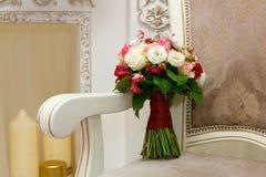 Ramo hermoso de la boda de rosas rojas y blancas en silla Foto de archivo