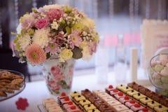 Ramo hermoso de la flor en florero en la tabla por completo de dulces fotos de archivo libres de regalías