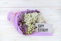 Ramo hermoso de lila con la tarjeta del feliz cumpleaños imagenes de archivo