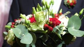 Ramo hermoso de rosas rojas en manos de hombres en chaqueta en un lazo rojo y una camisa blanca ramo hermoso de flores adentro almacen de video