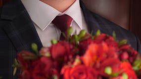 Ramo hermoso de rosas rojas en manos de hombres en chaqueta en un lazo rojo y una camisa blanca ramo hermoso de flores adentro metrajes