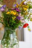 Ramo hermoso de wildflowers brillantes en el florero de cristal Imagenes de archivo