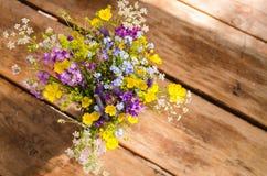 Ramo hermoso de wildflowers brillantes en un fondo de madera de la tabla Imagen de archivo