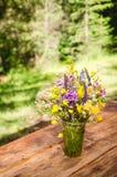 Ramo hermoso de wildflowers brillantes en una tabla de madera Foto de archivo