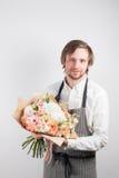 Ramo hermoso hecho de diversas flores en mano del hombre joven flor colorida de la mezcla del color Ropa de trabajo en un blanco Imagen de archivo