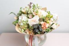 Ramo ligero lindo con las rosas del jardín y las flores mezcladas en la tabla rosada Fotos de archivo