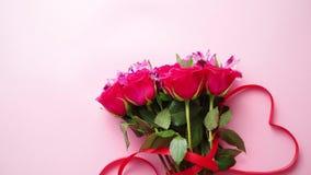 Ramo mezclado de las flores con las rosas y arco en forma de corazón en fondo rosado