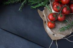 Ramo molhado do tomate com alecrins no papel do cozimento foto de stock