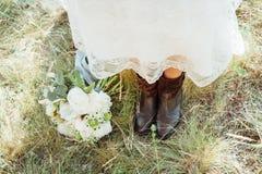 Ramo nupcial cerca de sus pies en la hierba Imagen de archivo libre de regalías