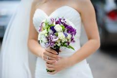 Ramo nupcial de flores púrpuras y blancas en las manos de la novia Fotos de archivo libres de regalías