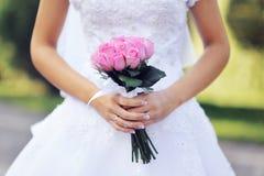 Ramo nupcial de la boda rosada de rosas en las manos de la novia Imagen de archivo libre de regalías