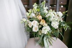 Ramo nupcial El ` s de la novia Hermoso de las flores blancas y del verdor, adornado con la cinta de seda, miente en vintage Fotos de archivo libres de regalías
