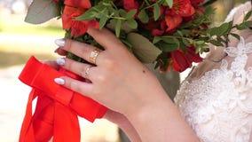 Ramo nupcial rojo hermoso en las manos de la novia joven vestidas en el vestido que se casa blanco Cámara lenta chica joven en a metrajes
