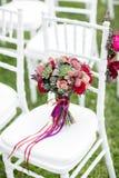 Ramo nupcial rojo imponente en la silla blanca Ceremonia de boda Mezcla de succulents, de orquídeas y de rosas Fotografía de archivo libre de regalías