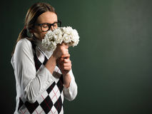 Ramo que huele del empollón femenino joven de flores fotografía de archivo libre de regalías