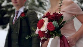 Ramo que lleva de la novia de flores hechas de las rosas blancas y rojas Pares de la boda que caminan llevando a cabo las manos e