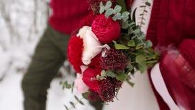 Ramo que lleva de la novia de flores hechas de las rosas blancas y rojas Pares jovenes de la boda que caminan en bosque nevoso du