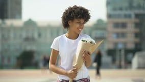 Ramo que se sostiene femenino afroamericano contento y disfrutar del aroma agradable metrajes