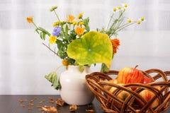 Ramo rústico brillante de las flores, manzanas en un cuenco de mimbre Fotos de archivo