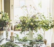 Ramo real del verano hecho de las flores salvajes del campo en una tabla en una sala de estar moderna por la ventana Foto de archivo