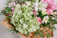 Ramo rico con la hortensia en mano de la mujer rosas coloridas y diversas flores de la mezcla del color Fotografía de archivo libre de regalías