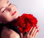 Ramo rojo de las rosas de la explotación agrícola femenina hermosa Imagen de archivo libre de regalías
