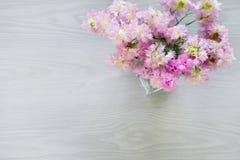 Ramo rosado de la flor en florero en fondo de madera gris Fotografía de archivo