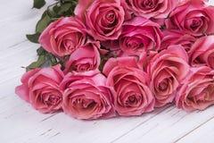 Ramo rosado de las rosas en el fondo de madera blanco Foto de archivo libre de regalías