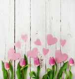 Ramo rosado de los tulipanes con los corazones de papel en fondo de madera Fotos de archivo