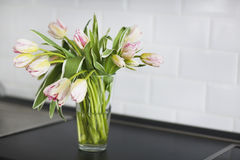 Ramo rosado de los tulipanes en el florero de cristal en la cocina Imagen de archivo