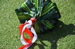 Ramo verde de la boda con las cintas del escarlata y del blanco en la hierba Fotos de archivo