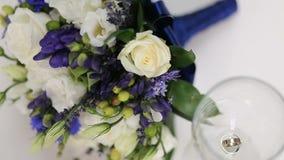 Ramo y anillos de bodas nupciales hermosos en un vidrio de vino almacen de metraje de vídeo