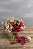 Ramo y boutonniere nupciales Flores del rojo y del color del melocotón Foto de archivo