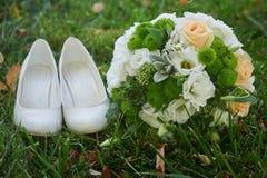 Ramo y el bride& x27 de la boda; zapatos blancos de s en hierba Imagen de archivo