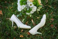 Ramo y el bride& x27 de la boda; zapatos blancos de s en hierba Foto de archivo