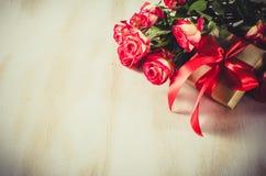 Ramo y presente de las rosas rojas en la tabla de madera Fotos de archivo libres de regalías