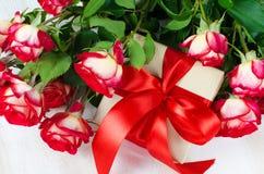 Ramo y presente de las rosas rojas en la tabla de madera Imágenes de archivo libres de regalías