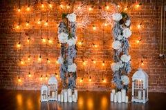 Ramos coníferos com arbustos da hortênsia, velas e as ampolas em um fundo do tijolo imagens de stock royalty free