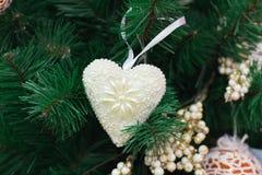 Ramos de árvore do Natal com coração branco e os ornamento dourados Foto de Stock