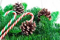 Ramos de árvore do Natal com os bastões de doces na mesa de madeira branca Espaço liso da configuração para o texto imagem de stock