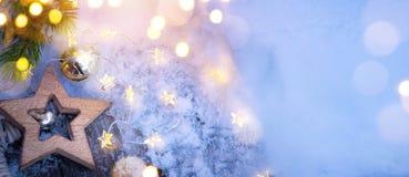 Ramos de árvore nevados azuis do fundo e do abeto do Feliz Natal com luzes dos feriados fotografia de stock royalty free