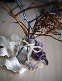 Ramos de árvore secos em um frasco transparente com uma corda amarrada em uma curva nela que está na superfície de madeira Imagens de Stock