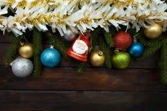Ramos de árvore verdes do Natal em um fundo de madeira escuro Fundo do ano novo com bolas coloridos e ouropel e sino do ouro T Fotografia de Stock