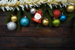 Ramos de árvore verdes do Natal em um fundo de madeira escuro Fundo do ano novo com bolas coloridos e ouropel e sino do ouro T Imagens de Stock Royalty Free