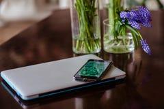 Ramos de flores en floreros simples elegantes en una tabla cerca del teléfono móvil y del ordenador portátil fotos de archivo