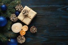 Ramos de uma árvore, cones do pinho das decorações do Natal e do Natal, brinquedos azuis do Natal em um fundo de madeira a de emp Imagens de Stock