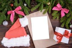 Ramos do abeto, curva cor-de-rosa da fita, tampão do Natal, envelope e bolas do Natal Fundo do ano novo imagem de stock