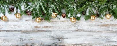 Ramos do Natal e ornamento dourados com neve no whit rústico Imagem de Stock